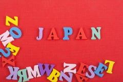 JAPANSKT ord på röd bakgrund som komponeras från träbokstäver för färgrikt abc-alfabetkvarter, kopieringsutrymme för annonstext Arkivbild