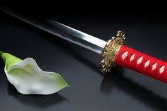 Japanskt samurajsvärd och härlig blomma Fotografering för Bildbyråer