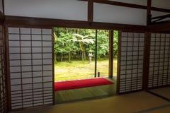 Japanträdgård med stenlyktan som ses till och med glidningsdörrarna Arkivfoton