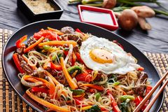 Japchae korean dish in a black plate, close up. Japchae korean dish: glass noodles with stir fried pepper, carrot, spinach, onion, egg, garlic, shiitake stock image