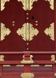 Japoński czerwony drzwi z złoto poręczami w frontowym tle i szczegółami obrazy stock