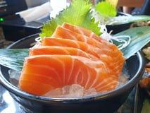 Japoński jedzenie styl, zakończenie w górę łososiowego plasterka na bambusie opuszcza na lodzie w czarnym pucharze fotografia stock