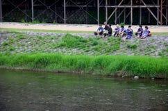 Japończycy siedzą i opowiadają przy brzeg rzeki Kamo rzeka obraz stock