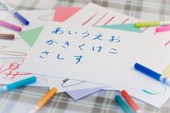 Japończyk; Dzieciaki Pisze Japońskiego abecadło charakteru dla praktyki fotografia royalty free