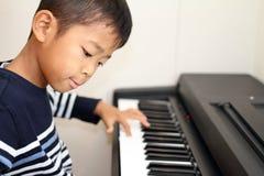 Japońska chłopiec bawić się pianino zdjęcia royalty free