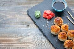 Japońska kuchnia Piec suszi z kraba serem na kamiennej cegiełce w ciemnym drewnianym tle i mięsem Odgórny widok z kopii przestrze Fotografia Stock