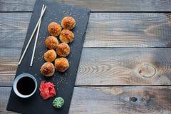 Japońska kuchnia Piec suszi z kraba serem na kamiennej cegiełce w ciemnym drewnianym tle i mięsem Odgórny widok z kopii przestrze Zdjęcia Stock