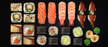 Japońska kuchnia Suszi i rolki ustawiający nad ciemnym tłem Obrazy Stock