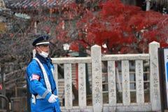 Japońska policja drogowa w błękicie munduruje spełnianie obowiązki na ulicie obrazy stock