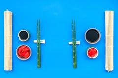 Japoński karmowy kulinarny ustawiający z soja kumberlandem, imbir, bambus wtyka dla suszi na błękitnego tła odgórnym widoku zdjęcia stock