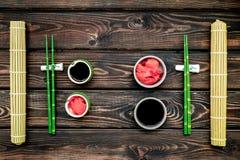 Japoński karmowy kulinarny ustawiający z soja kumberlandem, imbir, bambus wtyka dla suszi na drewnianego tła odgórnym widoku obraz stock