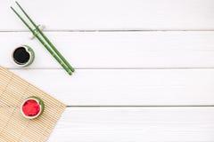 Japoński karmowy kulinarny ustawiający z soja kumberlandem, imbir, bambusowi kije dla suszi na białej drewnianej tło odgórnego wi zdjęcia royalty free