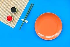 Japoński karmowy kulinarny ustawiający z soja kumberlandem, imbir, talerz, bambusowi kije na błękitnej tło odgórnego widoku kopii fotografia stock