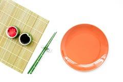 Japoński karmowy kulinarny ustawiający z soja kumberlandem, imbir, talerz, bambusowi kije na białej tło odgórnego widoku kopii pr zdjęcia royalty free