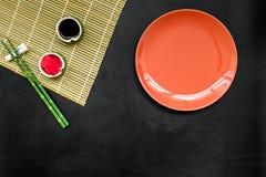 Japoński karmowy kulinarny ustawiający z soja kumberlandem, imbir, talerz, bambusowi kije na czarnej tło odgórnego widoku kopii p obrazy stock
