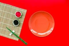 Japo?ski karmowy kulinarny ustawiaj?cy z soja kumberlandem, imbir, talerz, bambusowi kije na czerwonej t?o odg?rnego widoku kopii obraz stock