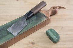 Japoński rzemienny rzemiosło nóż na rzemiennym nożowym strop z zieloną froterowanie mieszanką na drewnianej powierzchni Zdjęcia Stock