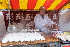 Japońskiego mężczyzna sprzedawania goheimochi ryżowy tort przy sklepem na ulicie Fushimi Inari świątynia Zdjęcie Stock