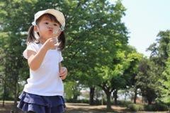 Japońskiej dziewczyny dandelion podmuchowi ziarna pod niebieskim niebem Obraz Stock