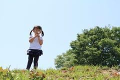 Japońskiej dziewczyny dandelion podmuchowi ziarna pod niebieskim niebem Zdjęcia Stock
