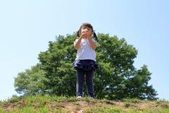 Japońskiej dziewczyny dandelion podmuchowi ziarna pod niebieskim niebem Obrazy Stock