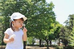 Japońskiej dziewczyny dandelion podmuchowi ziarna pod niebieskim niebem Zdjęcie Stock