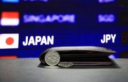 Japonés cientos monedas de los yenes en el JPY del anverso y una moneda que ponen en piso negro con la cartera negra y el tablero imágenes de archivo libres de regalías