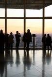 Japonés que mira la puesta del sol de un rascacielos Foto de archivo