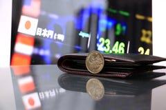 Japonés quinientos monedas de los yenes en el JPY del anverso en piso reflejo con la cartera negra y el tablero digital de dinero imagenes de archivo