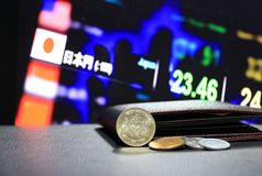 Japonés quinientos monedas de los yenes en el JPY del anverso y la pila de otras monedas del japonés en piso negro con la cartera fotografía de archivo libre de regalías