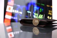 Japonés quinientos monedas de los yenes en el JPY reverso en piso reflejo con la cartera negra y el tablero digital de dinero del foto de archivo libre de regalías