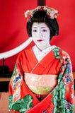 Japonês bonito Maiko, gueixa no retrato vermelho do traje fotos de stock royalty free