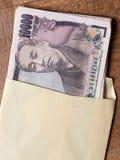 Japonês conta de 10000 ienes no envelope Fotografia de Stock Royalty Free