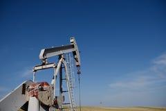 Jaque e campos brutos da bomba do local do poço de produção de petróleo contra céus azuis no xisto de Niobrara imagens de stock royalty free