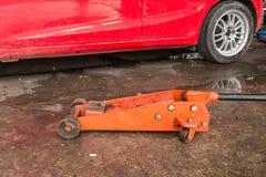Jaque hidráulico alaranjado do carro e carro vermelho Fotografia de Stock Royalty Free
