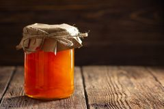 Jar with apricot jam. On wooden table royalty free stock photo