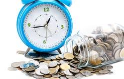 Jar of Asian coins with blue alarm clock Stock Photos