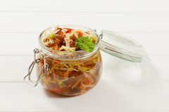 Jar of pickled vegetables. Jar of assorted pickled vegetables on white wooden background Stock Photography
