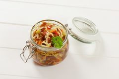 Jar of pickled vegetables. Jar of assorted pickled vegetables on white wooden background Royalty Free Stock Photography