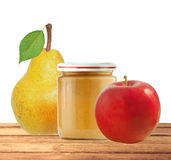 Jar of baby puree, apple and fresh yellow pear with green leaf i Royalty Free Stock Image