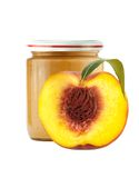 Jar of baby puree and half of fresh peach isolated on white Stock Images