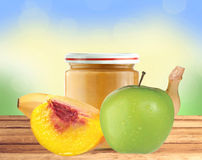 Jar of baby puree, peach, apple and banana on wooden table Royalty Free Stock Images