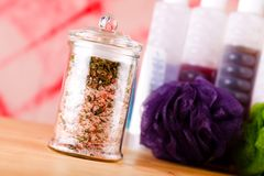 Jar with bath salt askew placed on wooden board Stock Photos