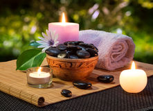 Jar of black stones and candles on bamboo mat. For massage stock photography