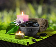 Jar of black stones and candles on mat. For massage royalty free stock photo
