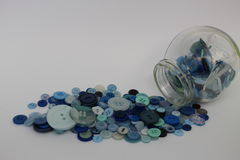 Jar of Blue Buttons. Used by a Haberdasher in the making of clothes. The jar contents is spilling outwards showing a variety of shades and sizes within the Royalty Free Stock Image