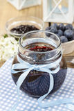 Jar of blueberry jam decorated with blue bow Stock Photo