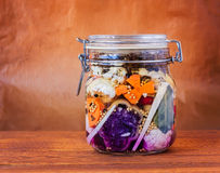 Jar of Brined Lacto-fermented Pickles. Jar of assorted brined lacto-fermented pickles on a wooden table stock images