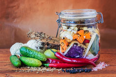 Jar of Brined Lacto-fermented Pickles. Jar of assorted brined lacto-fermented pickles on a wooden table surrounded by vegetables and spices stock image