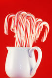 Jar of Candy Canes. Glass jar containing Christmas candy canes, red background stock photo